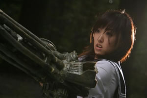 Machine gun girl suddenly realises that she need to scratch her nose, not easy